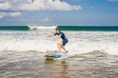 Den unga mannen, nybörjaresurfare lär att surfa på ett havsskum på bet royaltyfri foto
