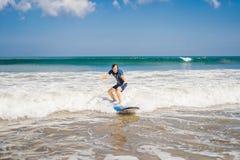 Den unga mannen, nybörjaresurfare lär att surfa på ett havsskum på bet arkivfoto