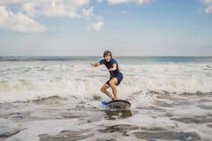 Den unga mannen, nybörjaresurfare lär att surfa på ett havsskum på bet fotografering för bildbyråer