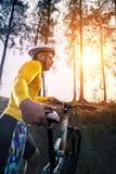 Den unga mannen och berget cyklar mot solljus för folkspor royaltyfri foto