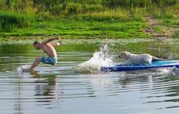 Den unga mannen och hunden i fartyget Hoppen från i vatten Fotografering för Bildbyråer
