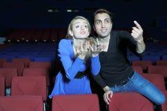 Den unga mannen och kvinnan håller ögonen på film och rotar för filmtecken Fotografering för Bildbyråer
