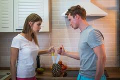 Den unga mannen och kvinnan har en gräla i kök hemma, parhushållstrid och familjsvårigheter royaltyfria bilder