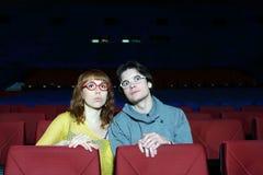 Den unga mannen och kvinnan i exponeringsglas håller ögonen på film och överraskning Arkivfoto