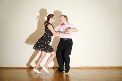 Den unga mannen och kvinnan i klänningdans på boogie-woogie festar. Arkivbilder