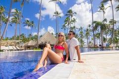Den unga mannen och kvinnan - koppla av nära simbassängen Royaltyfri Bild