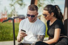 Den unga mannen och kvinnan som in sitter, parkerar och ser mobiltelefonskärmen arkivfoton