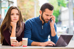 Den unga mannen och kvinnan som talar, har de gyckel, dem har i deras händer minnestavlan De dricker kaffe eller te Bärbar dator Royaltyfri Foto