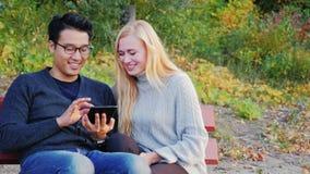 Den unga mannen och kvinnan som talar i parkera, tycker om minnestavlan Caucasian kvinna och en koreansk man arkivfilmer