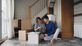 Den unga mannen och kvinnan tar selfie med smartphonen som gör hjärtaform med fingrar som sitter på golv av den nya lägenheten stock video