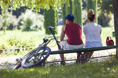Den unga mannen och kvinnor som sitter på en bänk parkerar in, i solig sommar Royaltyfria Bilder
