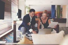Den unga mannen och lyckade chefer för kvinna arbetar samman med den bärbara netto-boken Royaltyfri Foto