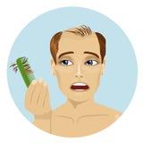 Den unga mannen oroade om hårkammen för innehavet för hårförlust som ser det stock illustrationer