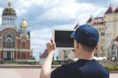 Den unga mannen på en stadsgata tar bilder av en kyrka Royaltyfri Bild