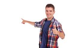 Den unga mannen presenterar något med tumen upp Royaltyfri Fotografi