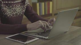 Den unga mannen räcker genom att använda anteckningsboken på en tabell stock video