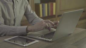 Den unga mannen räcker genom att använda anteckningsboken på en tabell lager videofilmer