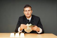 Den unga mannen räknar pengar Arkivbilder