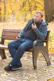 Den unga mannen röker tobakröret parkerar in Royaltyfria Foton