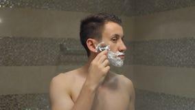 Den unga mannen rakar framme av spegeln Arkivbild