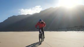 Den unga mannen rider en cykel på en sandstrand på kanariefågelöar Lanzarote Atlantic Ocean arkivfilmer