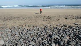 Den unga mannen rider en cykel på stora stenar in mot en sandstrand på kanariefågelöar Lanzarote Atlantic Ocean stock video