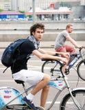 Den unga mannen rider en cykel som ser kameran Arkivfoton