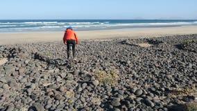Den unga mannen rider en cykel vid stora stenar in mot en sandstrand på kanariefågelöar Lanzarote Atlantic Ocean lager videofilmer