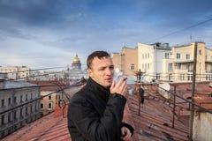 Den unga mannen röker cigarren på taket i Petersburg Royaltyfria Bilder