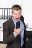 Den unga mannen ropar in i telefonen Fotografering för Bildbyråer
