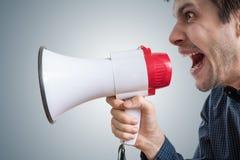 Den unga mannen ropar till megafonen och meddelar nyheterna Arkivfoton