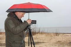 Den unga mannen rymmer det röda paraplyet och tar bilder av stranden på den regniga dagen royaltyfri foto