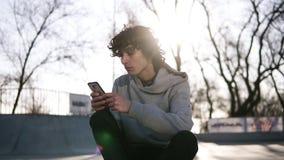 Den unga mannen rymmer en mobiltelefon, medan sitta i en skridsko som zonen i skridsko parkerar En grabb surfar rengöringsduken v lager videofilmer