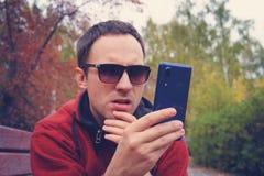 Den unga mannen rymmer en modern blå smartphone i hans hand och blick på skärmen med en förvånad blick Förvirring på royaltyfria bilder
