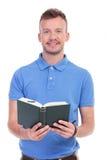 Den unga mannen rymmer hans bok Royaltyfri Bild