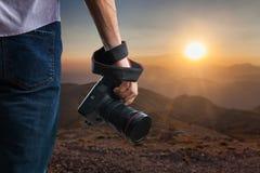 Den unga mannen rymmer den svarta moderna digitala kameran arkivbilder
