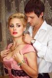 Den unga mannen sätter på smycken på härlig kvinna Fotografering för Bildbyråer