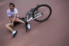 Den unga mannen sårade under att rida en cykel Royaltyfri Fotografi