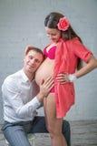 Den unga mannen satte huvudet på den gravida buken för frun i rött Arkivbild