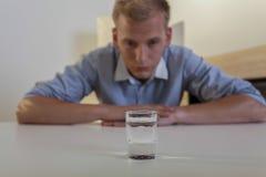Den unga mannen ser ett exponeringsglas av vodka Royaltyfri Fotografi