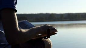 Den unga mannen ser familjfoto på en sjöbank i sommar lager videofilmer