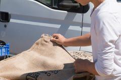 Den unga mannen ser gammal säckväv för kaffepåsar Arkivfoton