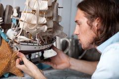 Den unga mannen ser modellen av seglingskeppet i tappninginre arkivbild