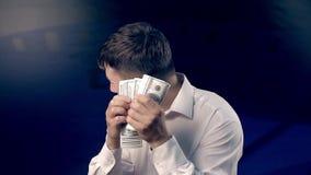 Den unga mannen ser tillbaka, medan räkna en stor mängd pengar lager videofilmer