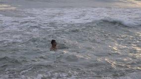 Den unga mannen simmar i ett tropiskt hav på solnedgången arkivfilmer
