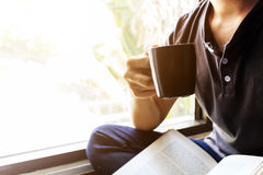 Den unga mannen sitter att läsa i fönstret arkivfoton