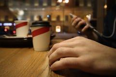 Den unga mannen sitter i ett kafé och läser meddelanden i telefonen arkivbild