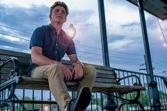 Den unga mannen sitter lyckligt parkerar på bänken med stråla tända för ljus pol upp aftonhimlen bak honom royaltyfria foton