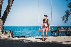 Den unga mannen sitter på en repgunga på stranden på Ko Samet Arkivfoton