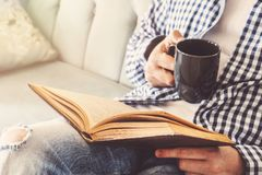 Den unga mannen sitter på en soffa och läser en bok, medan rymma en kopp kaffe eller ett te royaltyfri bild